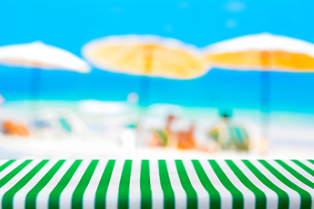 tablecloth: Table top covered with striped tablecloth on blurred summer beach background - can be used for display or montage your products Stock Photo