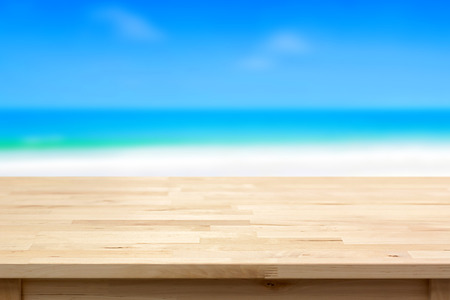 seashore: Wood table top on blur blue sea and sky background - can be used for montage or display your products
