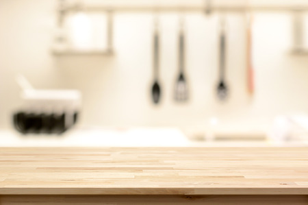 Wood table top (as kitchen island) on blur kitchen interior background - can be used for display or montage your products