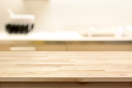 kitchen island: Wood table top (as kitchen island) on blur kitchen interior background - can be used for display or montage your products