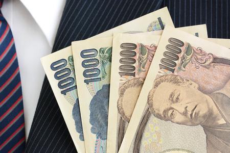 salarios: El dinero, el yen japonés (JPY) los billetes de banco, en traje de hombre de negocios de fondo