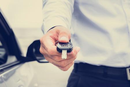 claves: Una, la imagen de tono vendimia hombre que da la llave del coche Foto de archivo