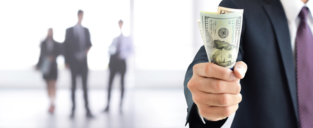 Businessman holding money, United States Dollar (USD) banknotes, in his fist - business and financial panoramic header background