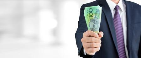 australian dollars: Businessman holding money, Australian dollar (AUD) banknotes, in his fist - business and financial panoramic header background