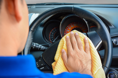 Een man schoonmaken auto stuurwiel met microfiber doekje, auto detaillering (valeting) -concept