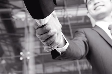 mergers: Handshake of businessmen in monochrome - greeting, dealing, mergers and acquisitions concepts