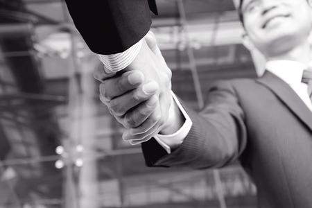 Handshake von Geschäftsleuten in monochrome - Gruß, Handel, Fusionen und Übernahmen Konzepte