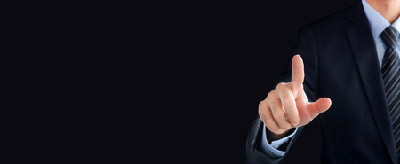 panoramic business: Businessman hand pointing on empty space on black panoramic (header) background - can be used as user interface or virtual screen background