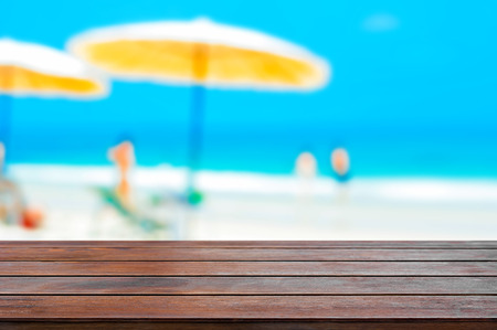 holiday display: Brown wood table top on blurred beach background, summer holiday background concept  - can be used for montage or display your products