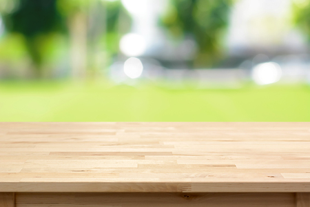 table wood: Wood table top on blurred green yard background - can be used for montage or display your products Stock Photo