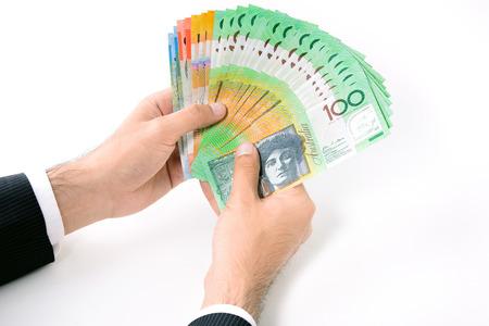show bill: Empresario manos sostienen el dinero, d�lar australiano (AUD) los billetes de banco, en el fondo blanco