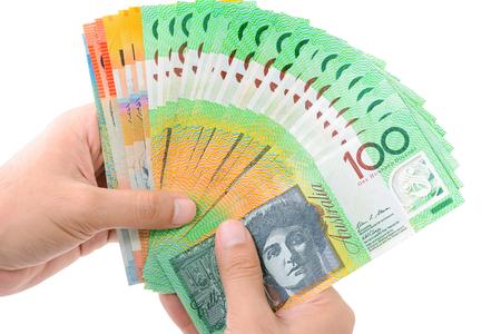 show bill: Manos que sostienen el dinero, d�lar australiano (AUD) los billetes de banco, aislado en fondo blanco