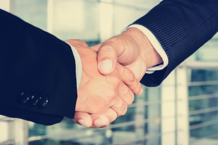 mergers: Handshake of businessmen - greeting, dealing, mergers and acquisition concept