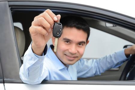 Glimlachende Aziatische man als bestuurder toont autosleutel (key focus)