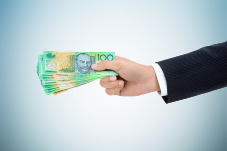 money exchange: Businessman hand giving  money, Australian dollar (AUD) banknotes, on white gray background