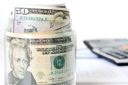 business funds: Money, US dollar bills, in the glass jar with blur calculator background - financial, business, investment and accounting concepts