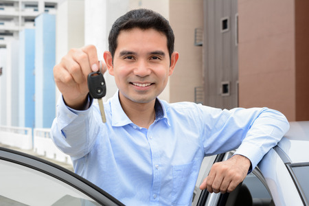 Smiling Asian man showing car key (face focused) Stock Photo