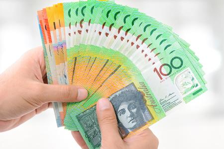 australian dollar notes: Hands holding money, Australian dollar (AUD) banknotes, on white gray background