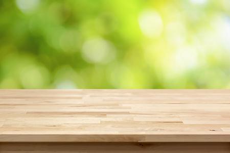 Holztischplatte auf Bokeh abstrakte grünen Hintergrund - können für die Montage oder gebraucht Sie Ihre Produkte werden