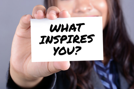 businesswoman card: WHAT INSPIRES YOU? message on the card shown by businesswoman