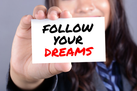 pursue: FOLLOW YOUR DREAMS message on the card shown by businesswoman Stock Photo