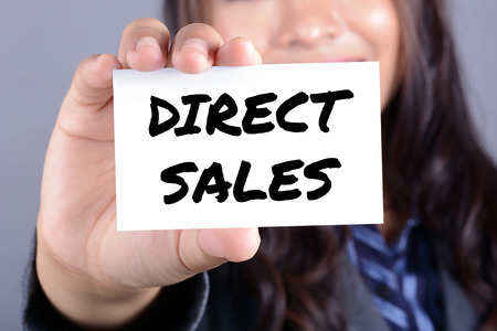 DIRECT SALES message on the card shown by businesswoman Stock Photo