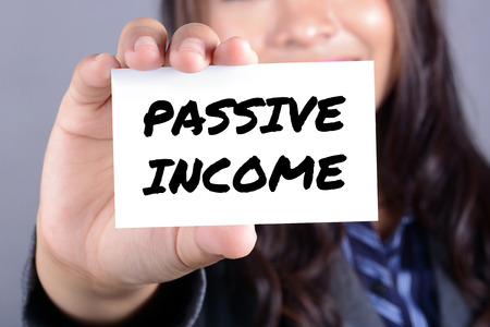 passive income: PASSIVE INCOME message on the card shown by businesswoman Stock Photo