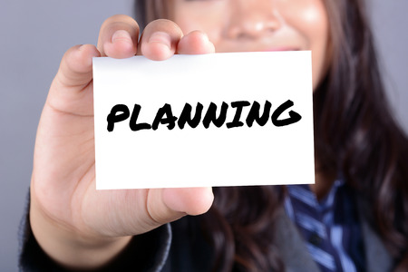 conspire: PLANNING word on the card shown by businesswoman