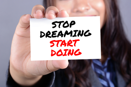 pursue: Businesswoman showing card with message STOP DREAMING START DOING