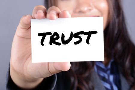 trustworthiness: TRUST word on the card shown by businesswoman Stock Photo
