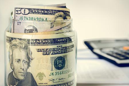 dollaro: Il denaro, banconote da un dollaro degli Stati Uniti, nel vaso di vetro con la calcolatrice sfocatura sfondo - finanziario, commerciale, investimenti e concetti di contabilit� Archivio Fotografico