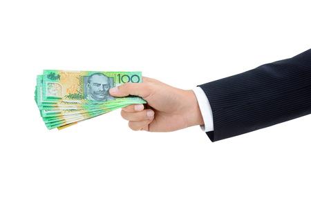 australian dollar notes: Hand of businessman giving money, Australian dollar (AUD) banknotes, on white background Stock Photo