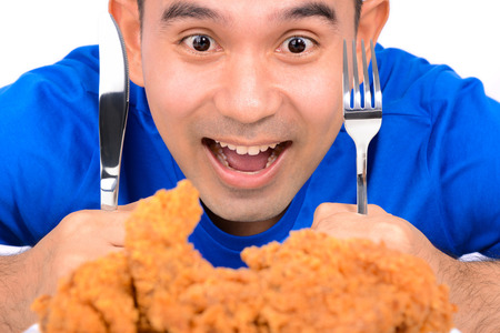 man mouth: A man holding knife and fork, staring at fried chicken, about to eat