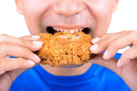 若い男が食べるフライド チキン