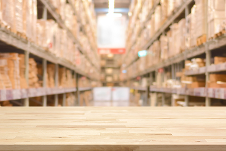 empty warehouse: Empty wood table top on blurred warehouse background - can montage or display your products