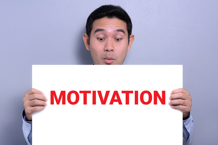 arouse: MOTIVATION word on white paper held by a man with excited face