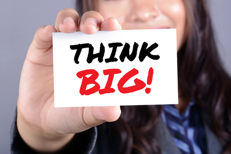 big women: THINK BIG! message on the card shown by a businesswoman