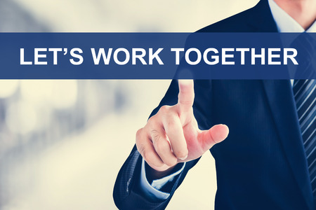 work together: Businessman hand touching LETS WORK TOGETHER message on virtual screen Stock Photo