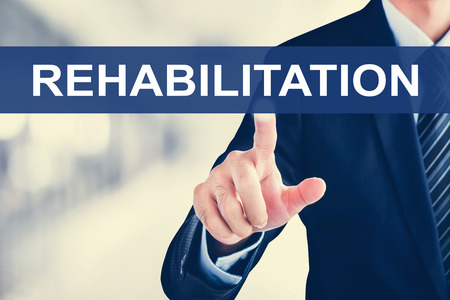 sick person: Businessman hand touching REHABILITATION word on virtual screen Stock Photo