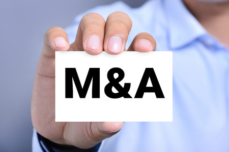 merger: M & A letters (or Merger and Acquisition) on the card held by a man hand