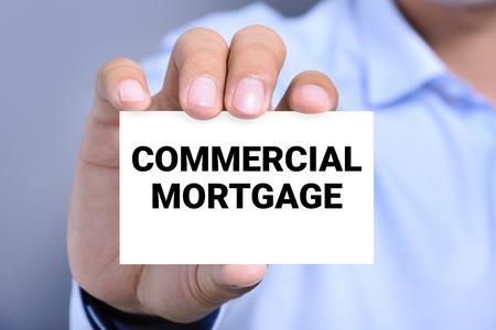 anuncio publicitario: mensaje de hipoteca comercial en la tarjeta sostenida por una mano del hombre Foto de archivo