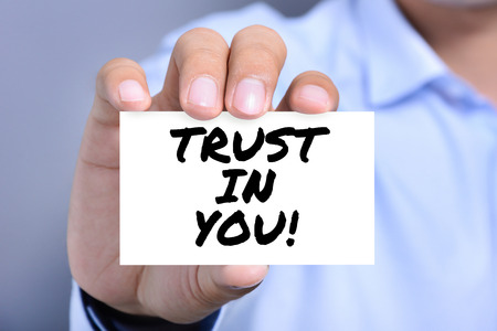 trustworthiness: TRUST IN YOU!, message on the card held by a man hand