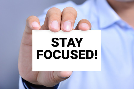 STAY FOCUSED! message on the card held by a man hand Imagens - 45616455