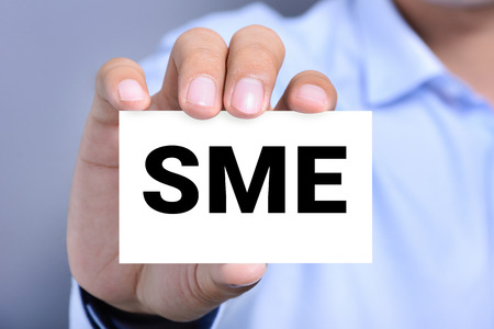enterprises: SME letters (or Small and Medium-sized  Enterprises) on the card shown by a man Stock Photo
