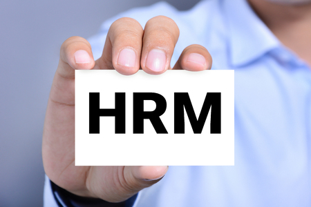 resources management: HRM letters (or Human Resources Management) on the card held by a man hand