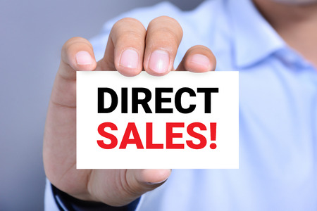 hard sell: DIRECT SALES! message on the card shown by a man