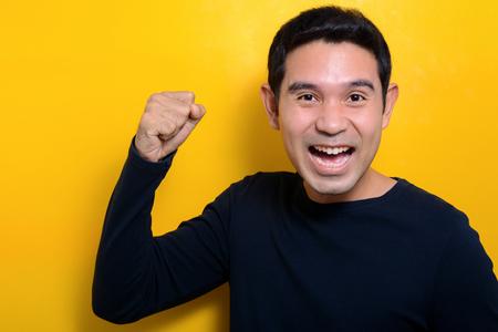 caras felices: Hombre joven que levanta su puño con la cara encantados sobre fondo amarillo Foto de archivo
