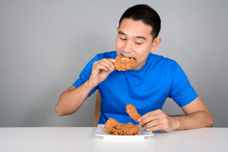 fried: Young man eating fried chicken on the table