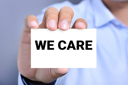 business concern: WE CARE, message on the card held by a man hand Stock Photo