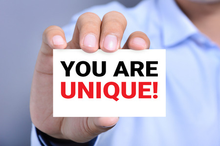 YOU ARE UNIQUE !, message on the card shown by a man hand